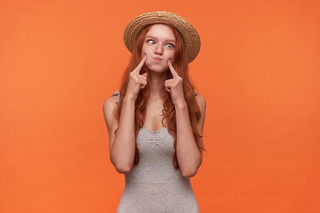オレンジ色の背景の上で楽しんで、頬を膨らませてカメラに目を細め、灰色のシャツとカンカン帽を身に着けている赤い長い髪の陽気な若い女性の肖像画