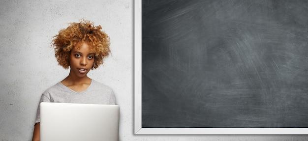 巻き毛と顔のピアスがラップトップコンピューターを使用して研究プロジェクトに取り組んでいる教室で空の黒板に立っている流行に敏感なアフリカの学生の肖像画。