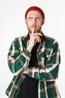 흰색 배경 위에 격리 된 서있는 동안 입술에 검지 손가락을 들고 모자와 격자 무늬 셔츠를 입고 hipster 수염 난된 남자의 초상화