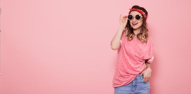 Портрет хипстерской девочки в очках на розовой стене