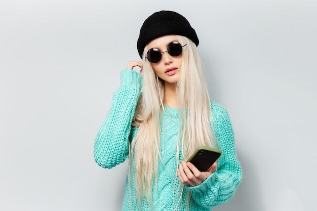 흰 벽에 손에 스마트 폰으로 hipster 여자의 초상화. 둥근 안경, 비니 모자와 청록색 스웨터를 입고 젊은 여자.
