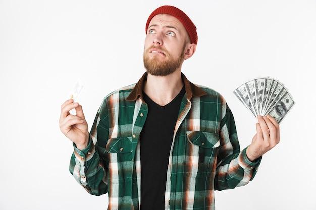 Портрет хипстера, держащего кредитную карту и поклонника долларовых денег, стоя изолированно на белом фоне