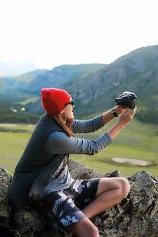 산을 여행하는 힙스터 남자의 초상화, 빨간 모자와 힙스터 옷을 입고, 사진을 찍습니다