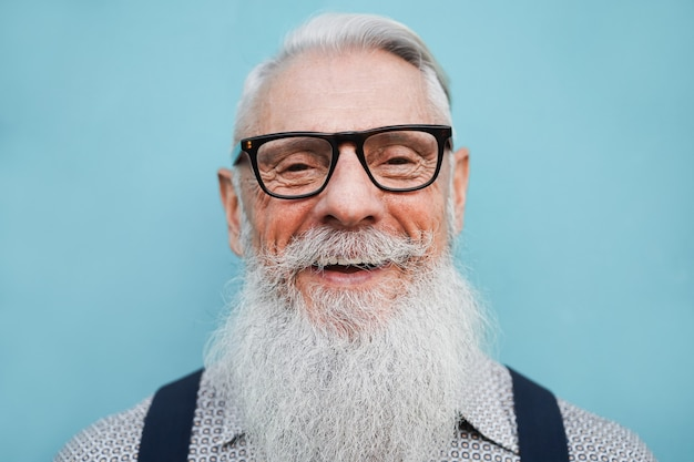 青い壁と眼鏡をかけている流行に敏感なシニアひげを生やした男の肖像画