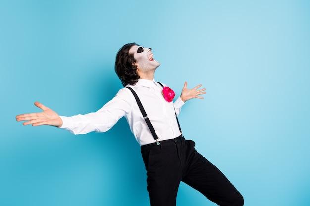 그의 잘 생긴 소름 끼치는 우아하고 쾌활한 쾌활한 꿈꾸는 부주의한 펑키 신사의 초상화는 즐겁게 춤을 추며 휴식을 취하며 노래를 부르며 격리된 밝고 생생한 선명한 파란색 배경