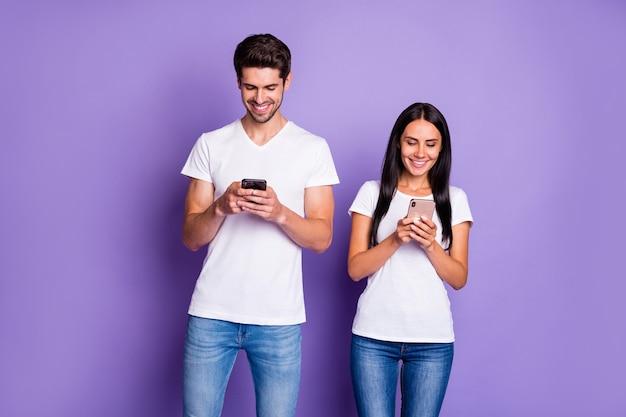 Портрет его он ее она милая привлекательная очаровательная милая веселая веселая пара, проводящая свободное время с помощью цифрового устройства, изолированного на фиолетово-лиловом пастельном фоне