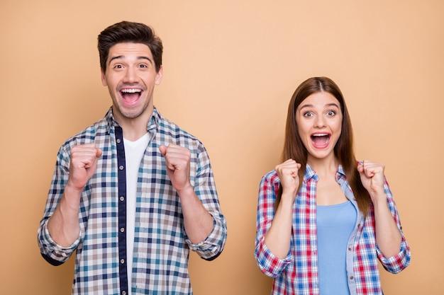 彼の肖像画彼女はベージュのパステルカラーの背景に分離された素晴らしい良いニュースを祝うチェックのシャツを着た彼女の素敵な魅力的な興奮した嬉しい陽気な陽気なカップル