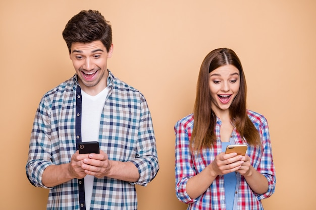 Портрет его он ее она красивая привлекательная сосредоточенная взволнованная пристрастившаяся веселая веселая пара в клетчатой рубашке просматривает интернет в интернете, изолированную на бежевом пастельном цветном фоне