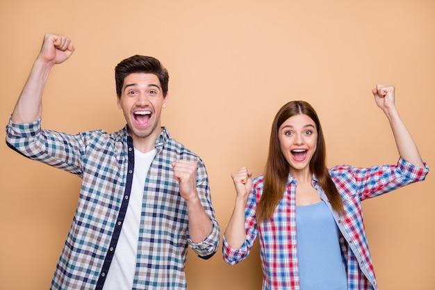 彼の肖像画彼女はベージュのパステルカラーの背景に分離された幸運を祝うチェックのシャツを着た彼女の素敵な魅力的な素敵な魅力的な陽気な陽気なカップルチーム