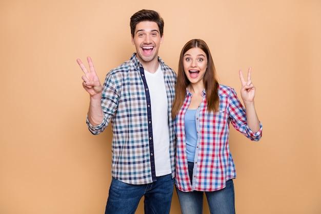 Портрет его он ее она милая привлекательная очаровательная очаровательная веселая веселая веселая пара в клетчатой рубашке, показывающая, что v-образный знак обнимает изолированно на бежевом пастельном цветном фоне