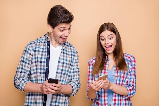 Портрет его он ее она милая привлекательная прекрасная веселая веселая радостная пара в клетчатой рубашке, использующая устройство, делающее быструю скорость 5 г, изолированную на бежевом пастельном цвете