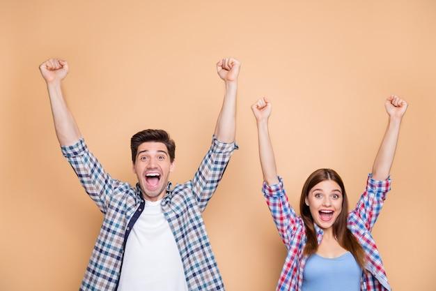 Портрет его он ее она милая привлекательная прекрасная довольная восторженная радостная веселая веселая пара в клетчатой рубашке празднует поднятие рук, изолированные на бежевом пастельном цветном фоне