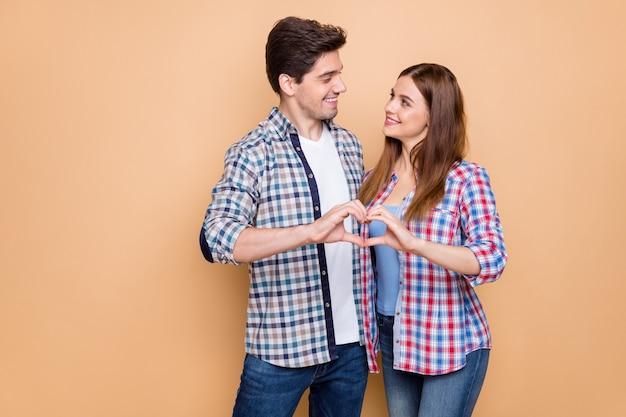 Портрет его он ее она милая привлекательная милая нежная милая нежная веселая пара в клетчатой рубашке, показывающая фигуру сердца, медовая луна, изолированная на бежевом пастельном цветном фоне
