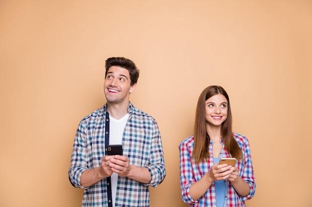 Портрет его он ее она милая привлекательная задумчивая творческая веселая веселая пара в клетчатой рубашке, создающая smm-пост, как следящий медиа-маркетинг, изолированный на бежевом пастельном цветном фоне