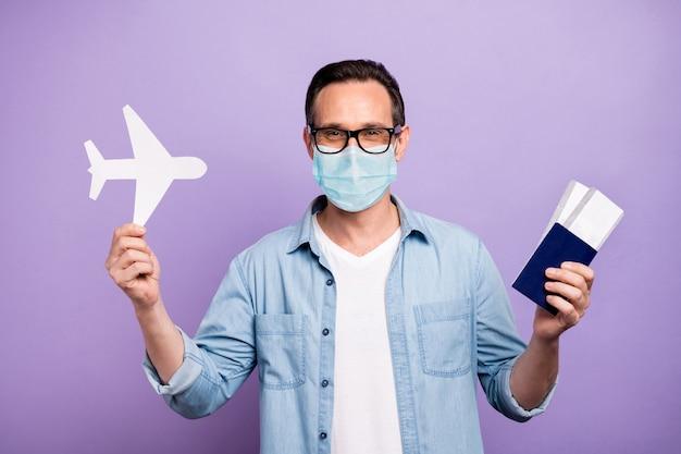 그의 성숙한 남자의 초상화는 해외 터키 이집트 바다 여름에서 출발하는 티켓 종이 카드 비행기를 들고 거즈 마스크를 쓰고 보라색 배경 위에 사회적 거리 항공사 비행기를 격리합니다