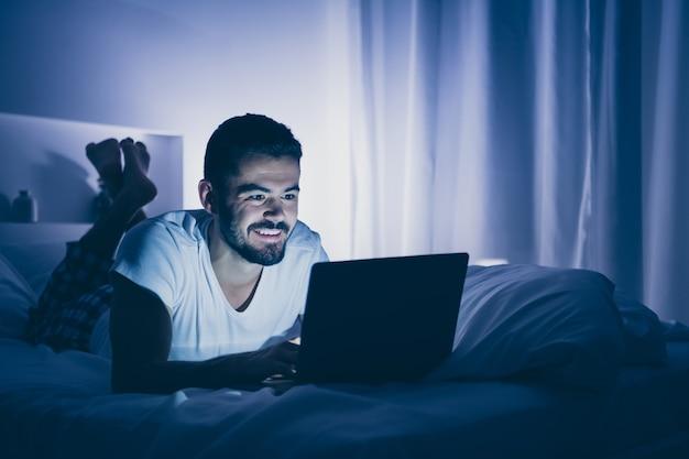 그의 초상화 그는 밤 늦은 저녁 집 어두운 방 플랫 하우스에서 시간을 보내는 디지털 노트북을 사용하여 침대에 누워 좋은 매력적인 쾌활한 쾌활한 수염 난 남자의 초상화