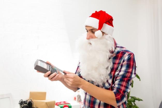 디지털 터미널 소매점 부티크 유료 패스를 들고 손에 들고 있는 그의 멋지고 쾌활한 뚱뚱한 산타의 초상화