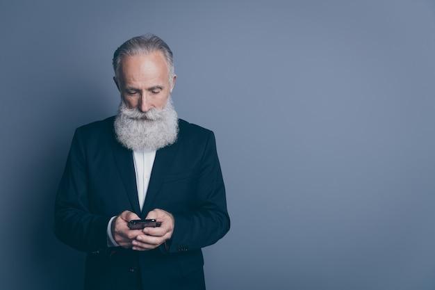 彼の素敵な魅力的なシックな上品な焦点を当てた濃い灰色のパステルカラーの背景の上に分離されたsmsメッセージを入力する現代のデバイスガジェットを使用してタキシードを身に着けている集中白髪の男の肖像画