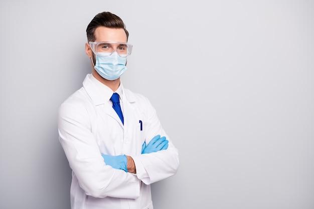 Портрет его он красивый привлекательный контент квалифицированный опытный доктор парамедик ученый стоматолог хирург физик скрестив руки, изолированные на светло-белом сером пастельном цвете