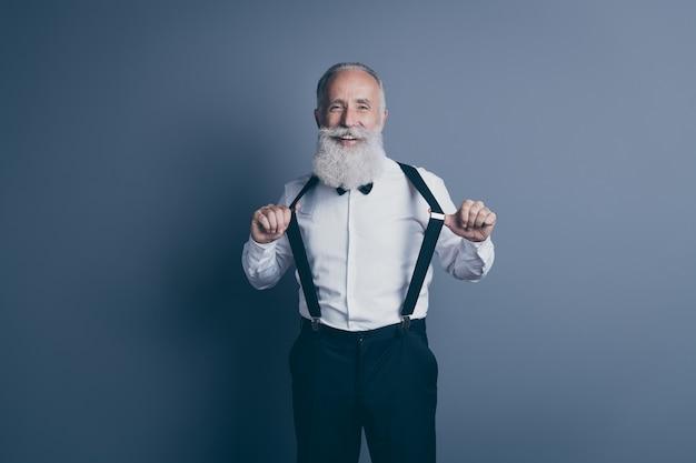 Портрет его симпатичного привлекательного крутого веселого веселого веселого фанк-седого человека, натягивающего подтяжки на одежде, изолированного на темно-сером пастельном фоне
