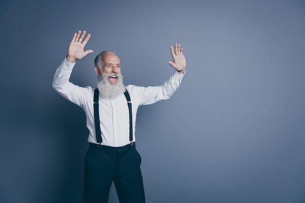 彼の素敵な魅力的なクールな陽気な陽気な嬉しい興奮した白髪の男の肖像画は、暗い灰色のパステルカラーの背景の上に分離された楽しみを持って手を振っています