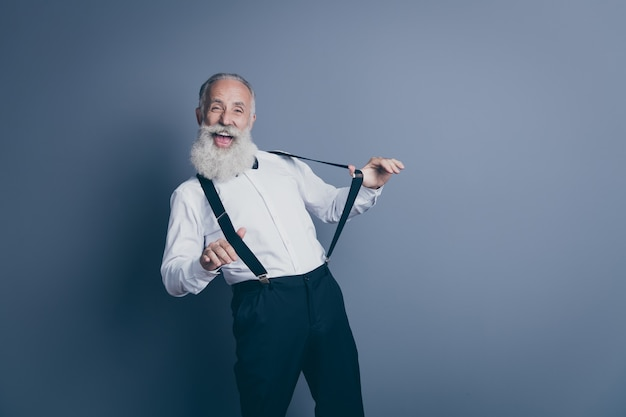 Портрет его симпатичного привлекательного сумасшедшего веселого веселого веселого фанк-седого мужчину, тянущего подтяжки, одежду, веселую одежду, изолированную на темно-сером пастельном цветном фоне