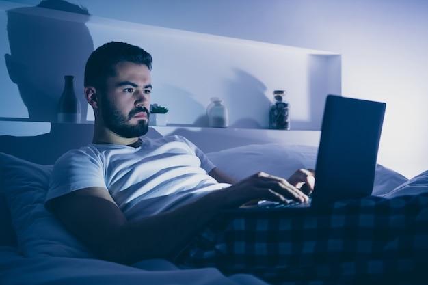 그의 초상화 그는 밤 늦은 저녁 집 어두운 방 플랫 하우스에서 디지털 노트북 블로깅을 사용하여 침대에 누워 좋은 매력적인 집중된 수염 난 사람의 초상화