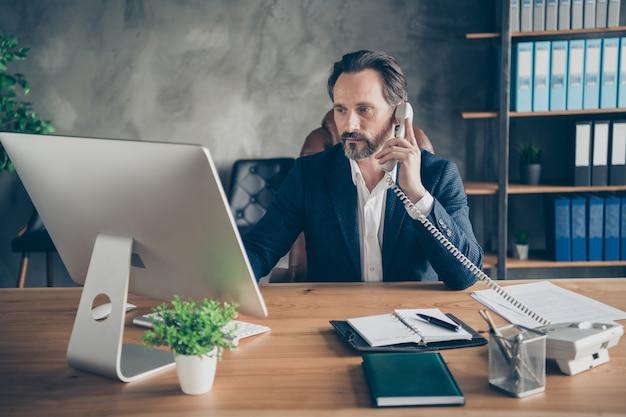 彼の素敵な魅力的な焦点を絞った忙しい人の保険販売の専門家の肖像画は、屋内のモダンなロフト産業職場ステーションでクライアント投資家の銀行サービスサポートアカウントをコンサルティングします