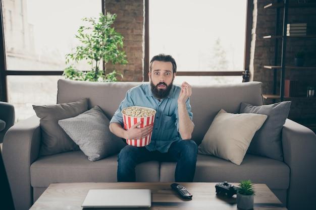 Портрет его симпатичного привлекательного испуганного нервного брюнетного парня, сидящего на диване и смотрящего сериал, проводящего время на промышленном чердаке в современном стиле, в интерьере, в доме, в помещении.