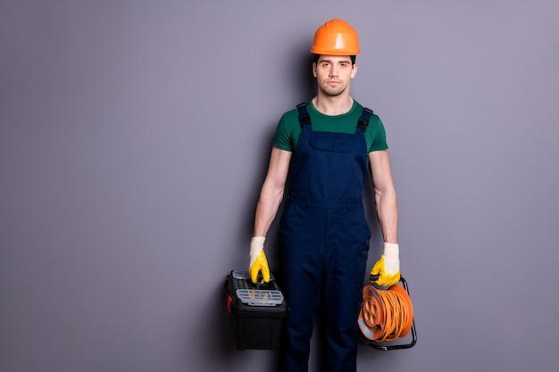 Портрет его симпатичного привлекательного серьезного профессионального квалифицированного контент-парня, услуги быстрого ремонта с инструментами, изолированными над серой пастельной стеной