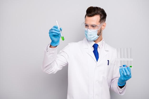 Портрет его он красивый привлекательный умный умный квалифицированный квалифицированный доктор ученый хирург держит в руках лампочки, делая аналитическую лабораторию, изолированную на светло-белом сером пастельном цвете