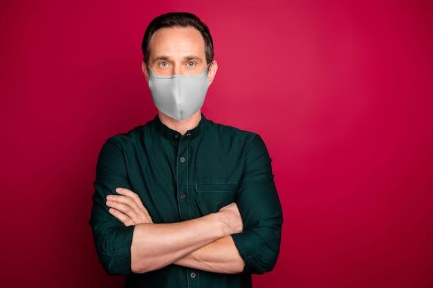 彼の素敵なコンテンツの肖像成熟した男フィナンシェceoボスチーフ腕を組んで安全マスクを身に着けている明るい鮮やかな輝き鮮やかなマルサラ赤い色の背景に分離されたウイルスmerscovを停止します