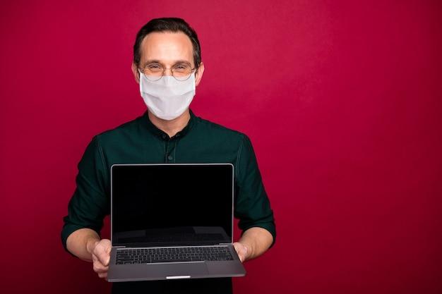 Портрет его опытного зрелого парня, держащего в руках ноутбук в маске безопасности, предотвращение mers cov, самоизоляция, социальная дистанция, изолированная на ярком ярком блеске, ярком красном цветном фоне