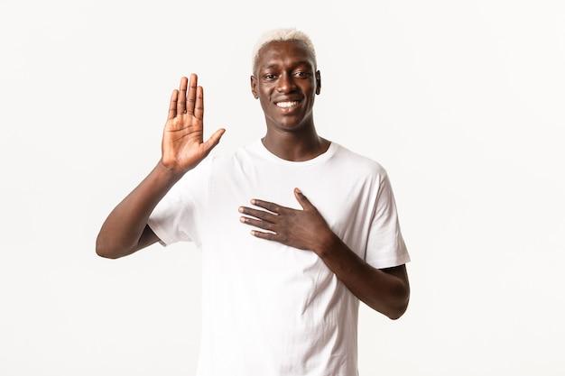 Портрет честного привлекательного афро-американского белокурого парня, поднимающего одну руку, а другую на сердце, обещающего, улыбаясь