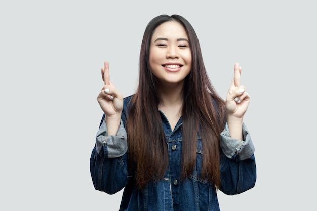 交差した指で立って、勝つために祈って化粧をしたカジュアルな青いデニムジャケットで希望に満ちた美しいブルネットアジアの若い女性の肖像画。明るい灰色の背景に分離された屋内スタジオショット。