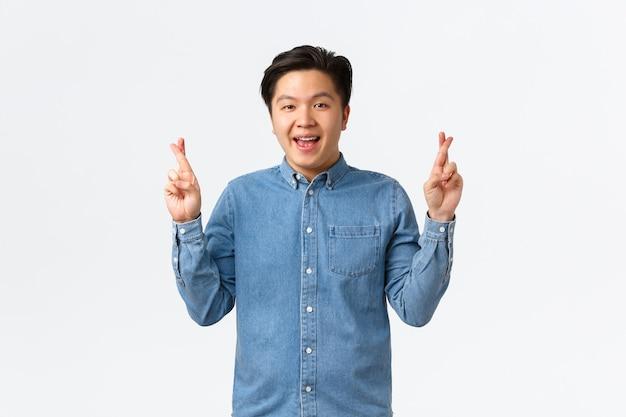 Портрет обнадеживающего оптимистичного азиатского мужчины с подтяжками, оптимистичного улыбающегося, верящего в мечту. парень загадывает желание со скрещенными пальцами, ожидая чуда, чувствуя себя удачливым, белый фон.