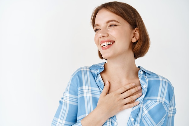 Портрет обнадеживающей красивой женщины с естественным макияжем, держащей руку на сердце, благодарной, улыбающейся, стоящей у белой стены