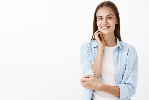 Портрет обнадеживающей нежной и женственной европейской брюнетки в синей блузке над белой футболкой, нежно касающейся лица и улыбающейся