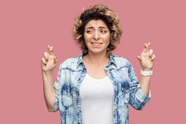 交差した指で立って、歯を食いしばって、心配そうな顔で目をそらしているカジュアルな青いシャツの巻き毛の希望に満ちた若い女性の肖像画。スタジオショット、ピンクの背景に分離。