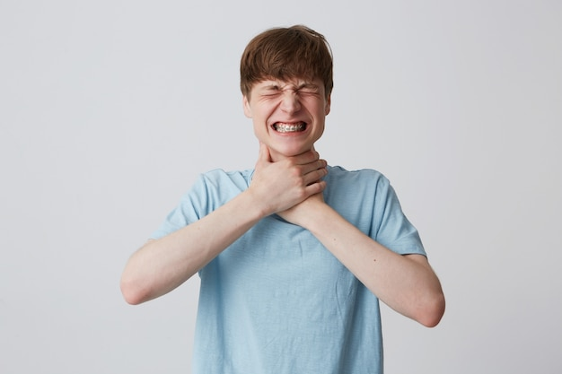Портрет безнадежного напряженного молодого человека с закрытыми глазами и брекетами на зубах носит синюю футболку