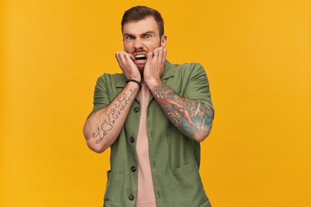 ブルネットの髪とあごひげを持つ恐ろしい、大人の男性の肖像画。緑の半袖ジャケットを着ています。入れ墨があります。恐怖で顔に触れる。黄色の壁に隔離