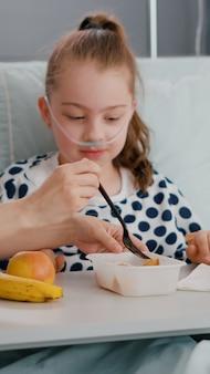 病棟で食事の昼食をとっている間、回復検査室のベッドに横たわっている入院中の小さな子供たちの肖像画。医療手術後に健康的な栄養ブレイクフェストを食べる病気の子供