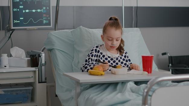 回復試験中に健康的な食事を食べてベッドで休んでいる入院中の小さな子供の肖像...