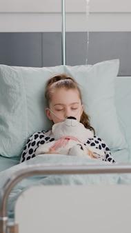 Портрет госпитализированного больного ребенка, засыпающего, держа в руках плюшевого мишку