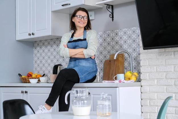 Портрет женщины домохозяйки в фартуке дома на кухне, улыбаясь счастливая женщина за столом