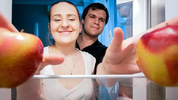 Портрет голодной пары, берущей еду из холодильника на кухне в ночное время. концепция диеты и здорового питания.