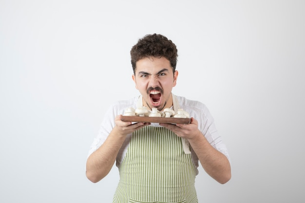 Портрет голодного мужского повара, держащего сырые грибы на белом