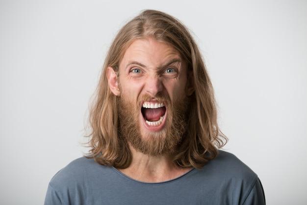 Портрет истерично раздраженного бородатого молодого человека со светлыми длинными волосами в серой футболке выглядит сумасшедшим и кричит изолированно над белой стеной