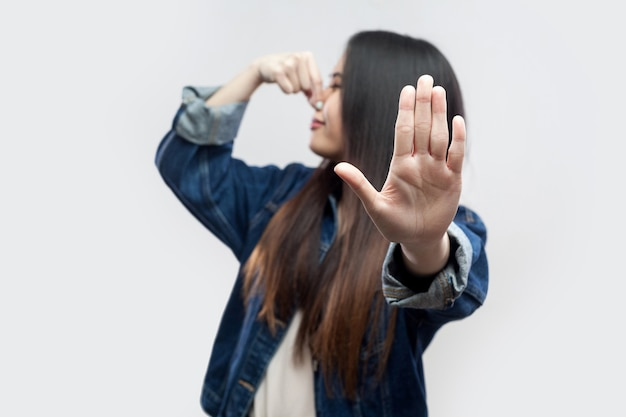 Портрет игнорирования молодой женщины брюнетки азиатской в повседневной синей джинсовой куртке с макияжем, стоящим, зажимая ее нос и показывающим руку с жестом остановки. крытая студия выстрел, изолированные на светло-сером фоне.