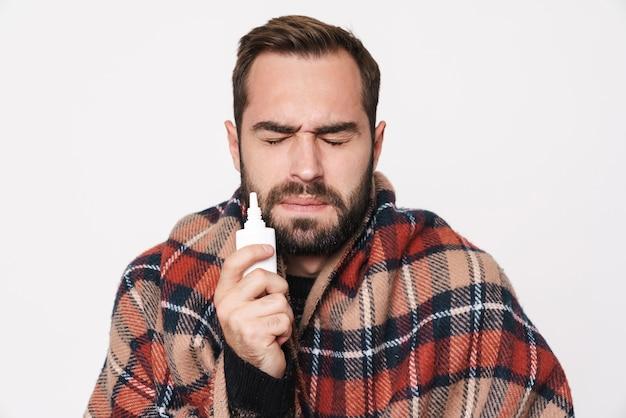 Портрет больного кавказского парня, завернутого в одеяло, с каплями в нос из-за гриппа, изолированного на белой стене